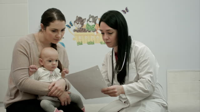 female pediatrician doctor shows some papers to woman with small baby video
