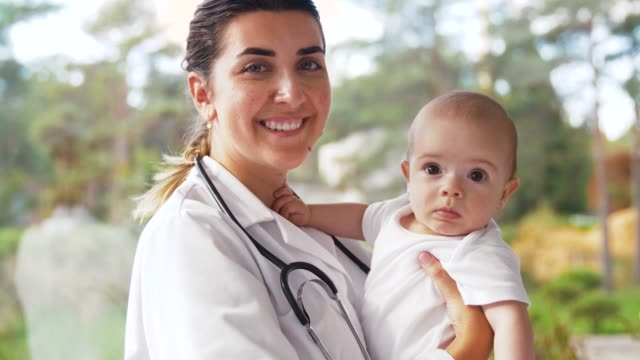 vrouwelijke kinderarts met baby in de kliniek video