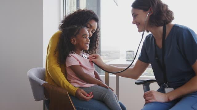 在醫院辦公室用聽診器聽女孩胸部聽力的女性兒科醫生 - surgeon 個影片檔及 b 捲影像