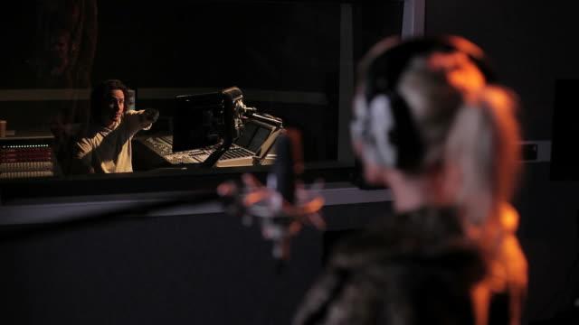 weibliche performing im tonstudio mit techniker - aufnahmestudio stock-videos und b-roll-filmmaterial