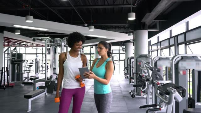 vídeos y material grabado en eventos de stock de entrenadora personal femenina mostrando negro joven cliente su entrenamiento en la tableta mientras habla - entrenador