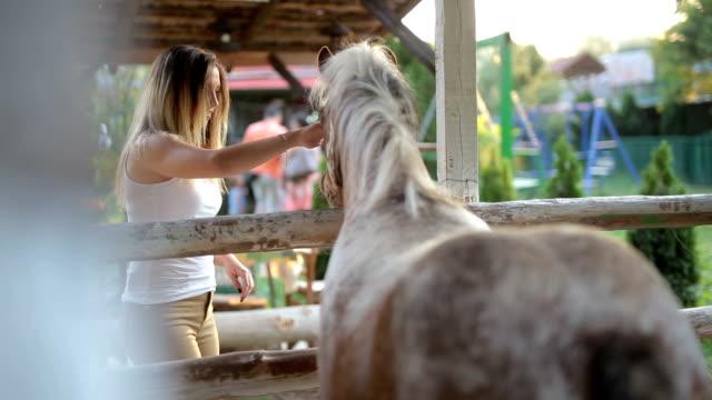 Female petting horse outside
