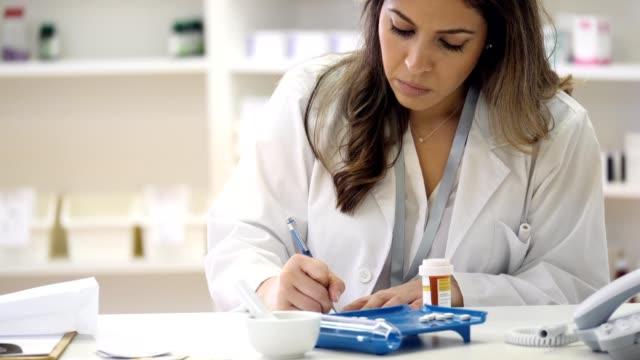female pharmacist fills patient's prescription - prescrizione medica video stock e b–roll