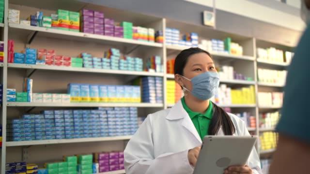 Female pharmacist giving medications to customer