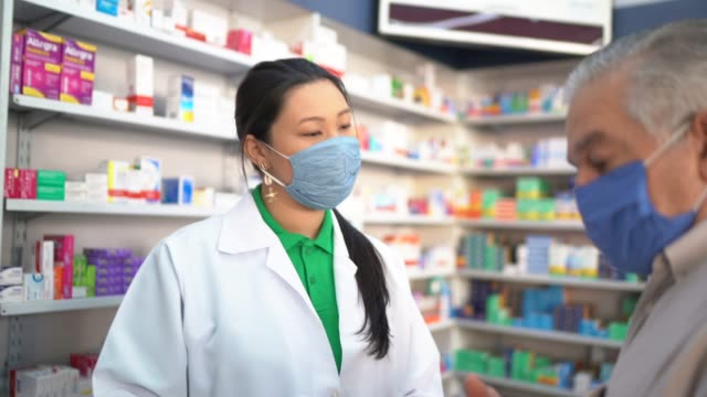 Female pharmacist giving medications to senior customer Female pharmacist giving medications to senior customer pharmaceutical industry stock videos & royalty-free footage