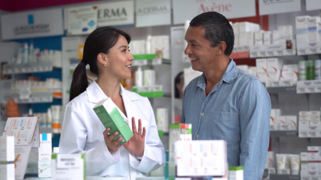 Female pharmacist helping a client with a product Female pharmacist helping a client with a product and handing him the product so he can look at it pharmacist stock videos & royalty-free footage