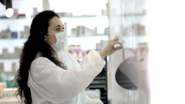 Female pharmacist wearing a surgical mask prepares the patient's medication Female pharmacist wearing a surgical mask prepares the patient's medication pharmaceutical industry stock videos & royalty-free footage