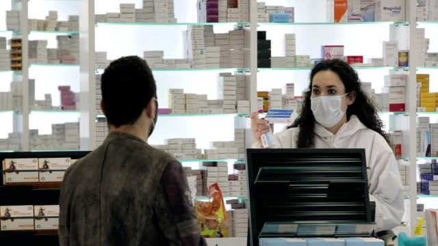 Female pharmacist wearing a surgical mask tells the male patient who wears a surgical mask how to use his medicine Female pharmacist wearing a surgical mask tells the male patient who wears a surgical mask how to use his medicine pharmaceutical industry stock videos & royalty-free footage
