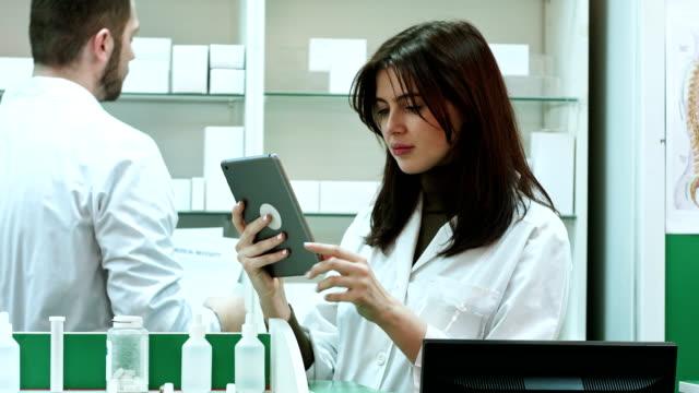 kvinnliga apotekspersonal med digital tablett söker efter medicinering - hospital studio bildbanksvideor och videomaterial från bakom kulisserna