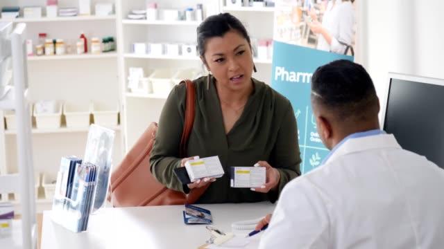 vídeos y material grabado en eventos de stock de la cliente ala de farmacia femenina le pide consejo a un farmacéutico masculino sobre los medicamentos de venta libre - receta instrucciones