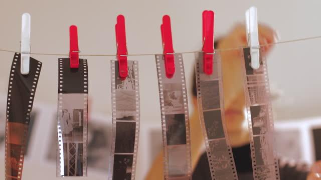 fotografinnen hängen filmstreifennegative, nachdem sie sie in der dunkelkammer entwickelt haben. - negativ bildart stock-videos und b-roll-filmmaterial