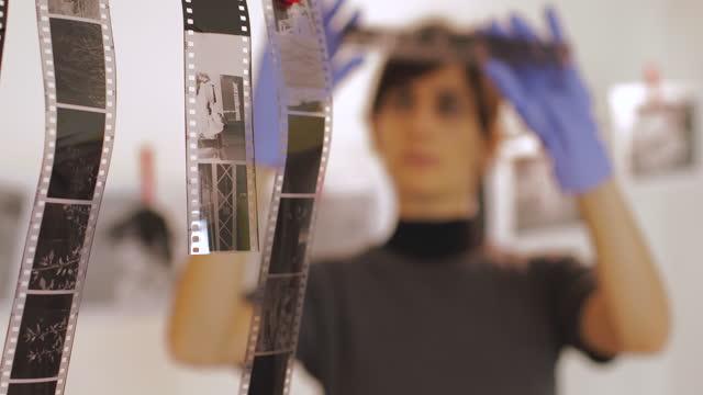 fotografinnen halten und bewerten filmnegative in der dunkelkammer. - negativ bildart stock-videos und b-roll-filmmaterial