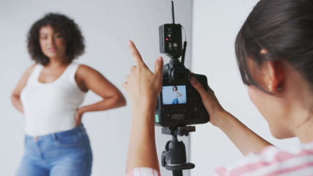 female photographer in digital studio shooting images on camera tethered to laptop computer - fotografika filmów i materiałów b-roll