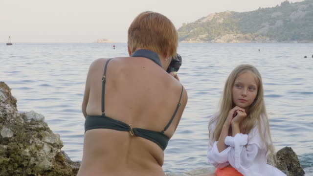 Female photographer taking picture of beautiful teenage girl at sea coast