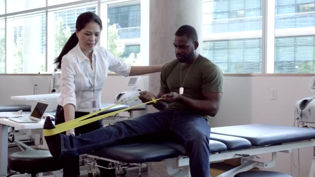 kvinnlig sjukgymnast arbetar i rehab center med skadad soldat - fysiotherapy bildbanksvideor och videomaterial från bakom kulisserna