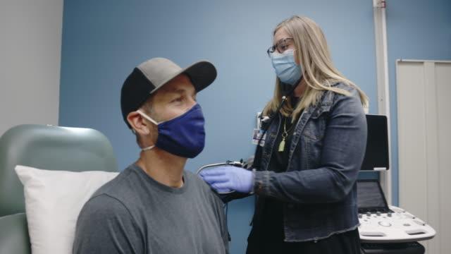 un'assistente medico femminile (pa) che indossa una maschera chirurgica entra in una sala d'esame di una clinica medica, indossa il suo stetoscopio e inizia ad ascoltare i polmoni di un maschio bianco mascherato sulla quaranta - ambulatorio medico video stock e b–roll