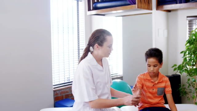 Female physiotherapist giving hand massage to boy patient 4k video