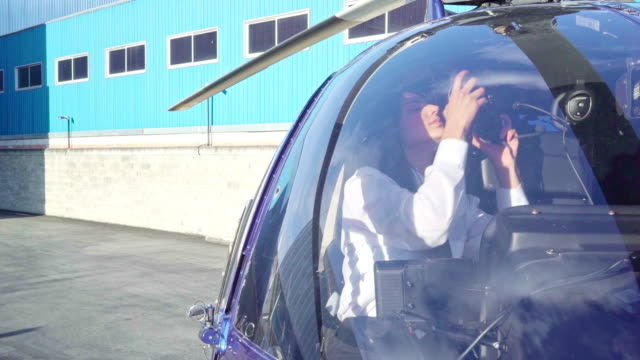 Female pilot climbed on top of the helicopter as she sits and prepares to take off
