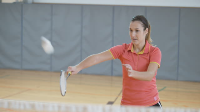 Female player playing indoor badminton video