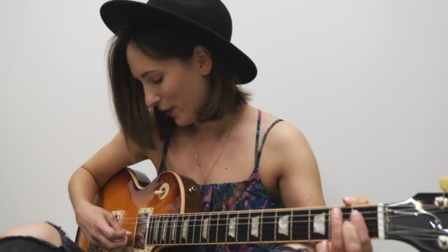 kvinna spelar på gitarr mot vit bakgrund. attraktiv kvinna sjunger låten. tusenden flicka öva att spela på gitarr. koncept för musikinstrument - gitarrist bildbanksvideor och videomaterial från bakom kulisserna