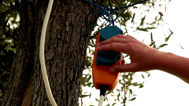 vidéos et rushes de femme brancher câble électrique dans la nature - vidéos de rallonge électrique
