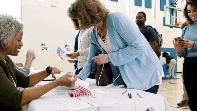 vidéos et rushes de une bénévole de bureau de vote féminin aide les électrices - démocratie