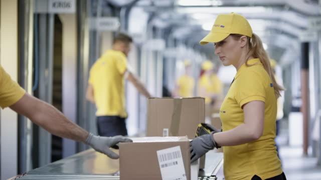 Female postal worker being handed parcel to scan on the conveyor belt video
