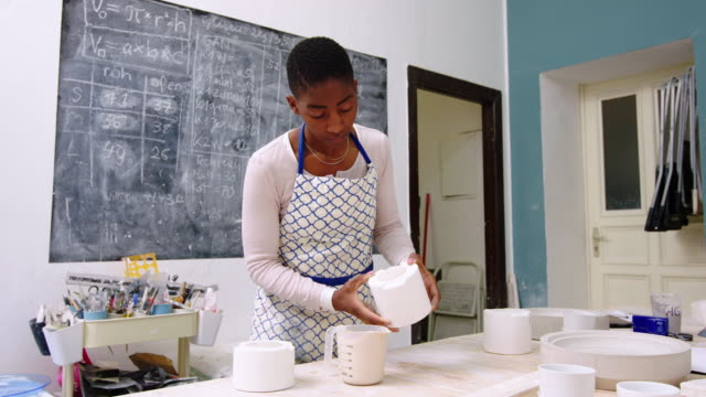 Female potter pouring clay from mould to plastic can