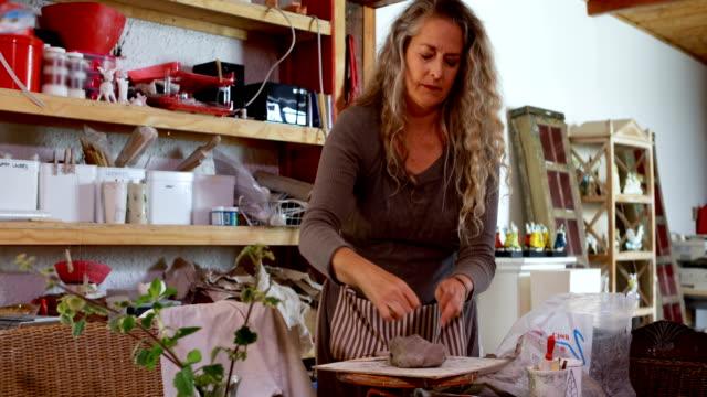 vídeos de stock, filmes e b-roll de feminino potter trabalhando na loja de cerâmica 4k - cerâmica artesanato
