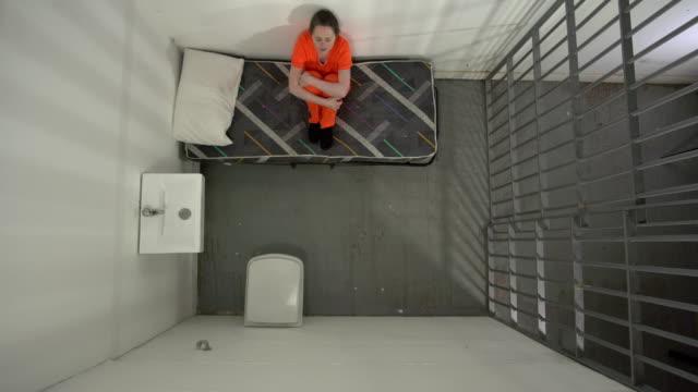 4k antenn: kvinnliga fången i fängelsecell lör på säng - fånga bildbanksvideor och videomaterial från bakom kulisserna