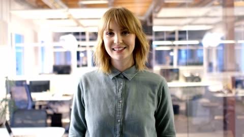 vidéos et rushes de femelle professionnelle souriant au bureau - portrait