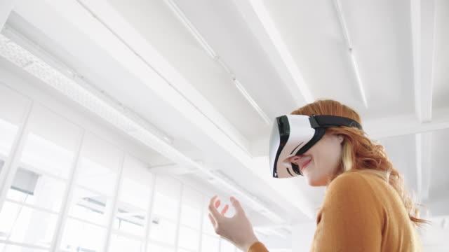 ofiste sanal gerçeklik gözlük kullanan kadın profesyonel - sanal gerçeklik stok videoları ve detay görüntü çekimi