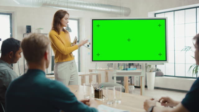 Female Project Manager Holds Meeting Presentation for a Team of Developers. She Shows Green Screen Interactive Whiteboard Device for Business Planning Concept. Young People Work in Creative Office Female Project Manager Holds Meeting Presentation for a Team of Developers. She Shows Green Screen Interactive Whiteboard Device for Business Planning Concept. Young People Work in Creative Office. Shot on 8K RED Camera. presentation stock videos & royalty-free footage