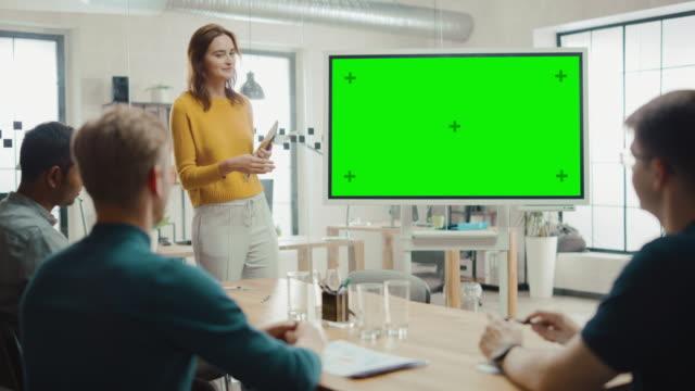 female project manager hält besprechungspräsentation für ein entwicklerteam ab. sie zeigt das interaktive whiteboard-gerät für die geschäftsplanung im grünen bildschirm. junge menschen arbeiten im kreativbüro - konferenzraum videos stock-videos und b-roll-filmmaterial