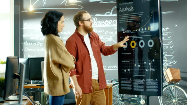 Female Project Manager Holds Meeting Shows Statistical Graphs and Charts on the Interactive Whiteboard Touchscreen Device. She Works in the Stylish Creative Agency. video