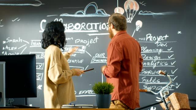 Chef de projet femelle cales Tablet PC parle avec le développeur de sexe masculin, ils discutent de Plan de projet dessiné sur un mur de Blackboard. Ils travaillent dans l'Agence Creative. - Vidéo
