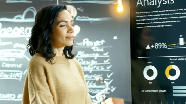 Chef de projet femme sourit et montre statistique des graphiques sur le tableau blanc interactif tactile périphérique. Elle travaille dans l'Agence Creative élégant. - Vidéo