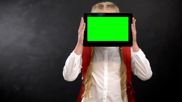 Female pupil closing face with green screen tablet, modern educational system