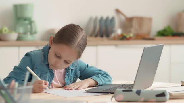ученица делает домашнюю задачу с помощью ноутбука - covid testing стоковые видео и кадры b-roll