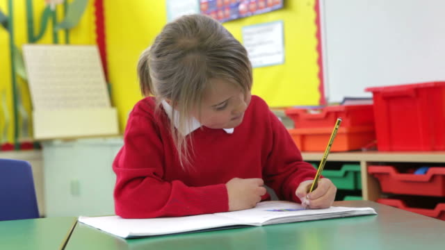 Female Pupil Practising Writing At Desk video