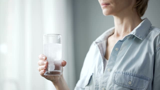 Female putting pill into glass with water and drinking it, woman's health video