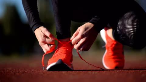 vidéos et rushes de coureur de course féminin attachant des lacets - chaussures