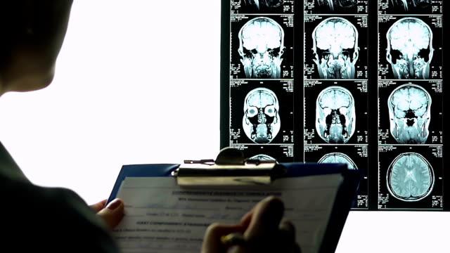 weibliche radiologe ausfüllen medizinischen bericht beschreibt gehirne mri, abschluss - medizinexamen stock-videos und b-roll-filmmaterial