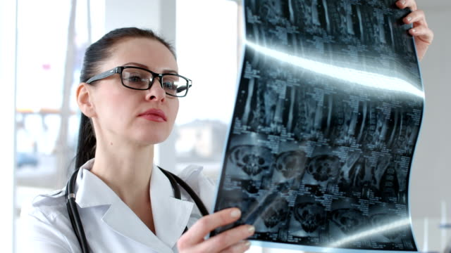 Female radiologist view mri scan video
