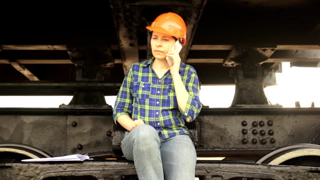 A female railway worker sits on the frame of the running gear of a freight car. video