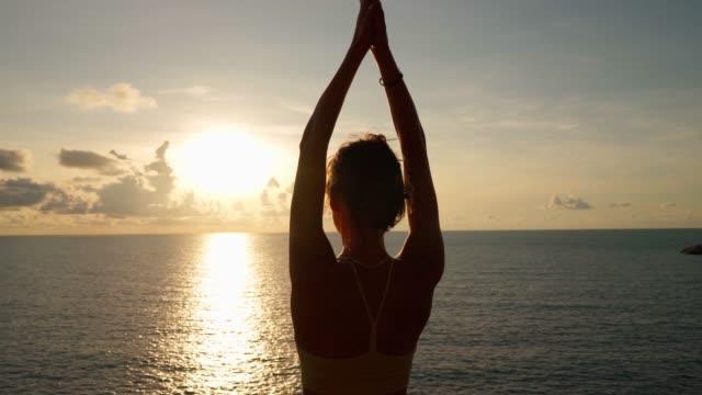 vídeos de stock, filmes e b-roll de mulher levantando os braços enquanto faz yoga - braço humano