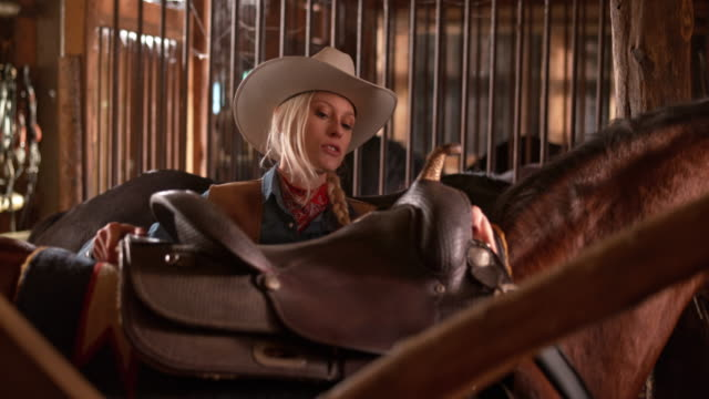ds female rancher putting a saddle on her horse - cowgirl video stock e b–roll