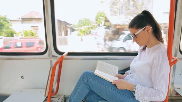 Female reading a book in the tram.