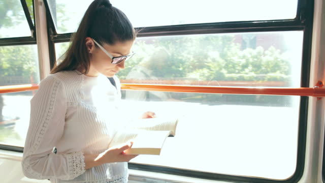 Female reading her favorite book in the tram.