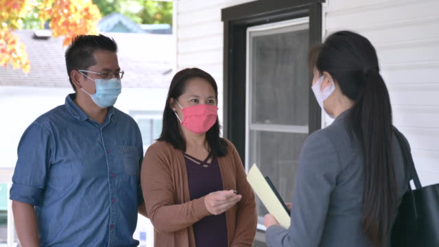 Female real estate agent meeting with potential buyers wearing masks Sale agent meeting with clients in front of a house for sale. All are wearing protective face masks to protect from the transfer of germs during the COVID-19 outbreak. home ownership stock videos & royalty-free footage